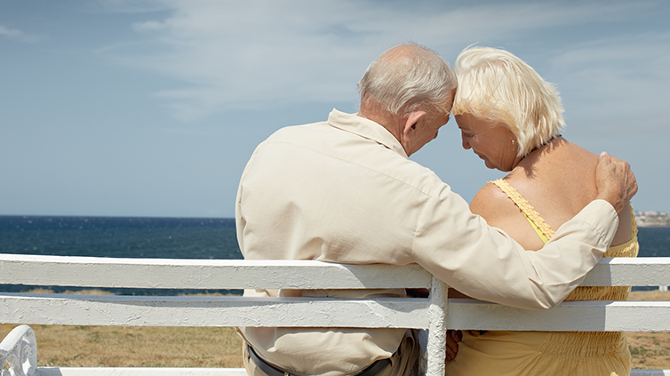 Elderly couple on a bench looking out to sea