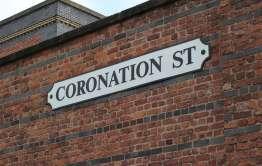 coronation street sign on brick wall