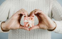 hands in heart shape holding gift wrapped donation