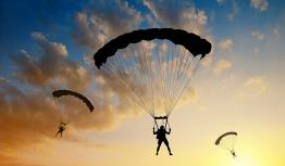 3 skydivers landing at dusk